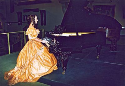 Clara Schumann (portrayed by J.M.Nauhaus during a guided tour in spring 2006) at her piano (Photo: Monika Heidemann)